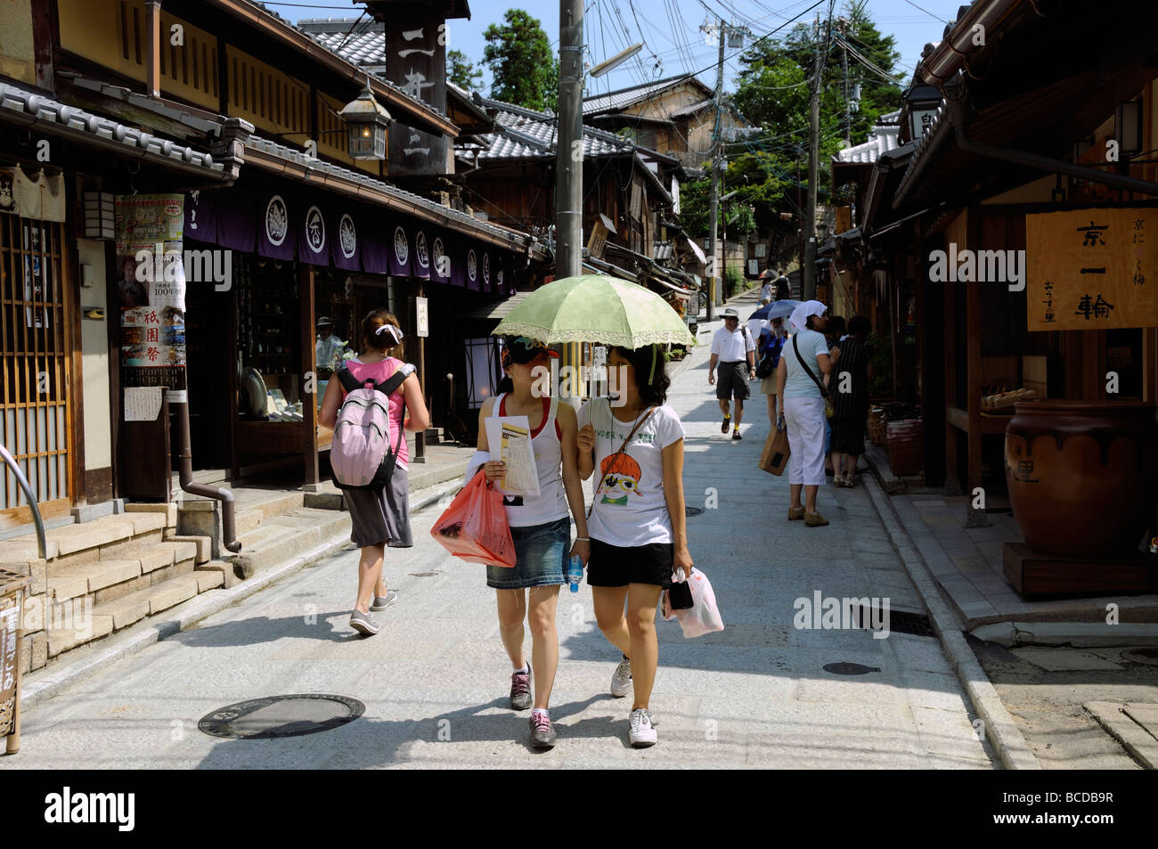 Kyoto Japan Japanese tourists with a umbrella walking in the street - Stock Image