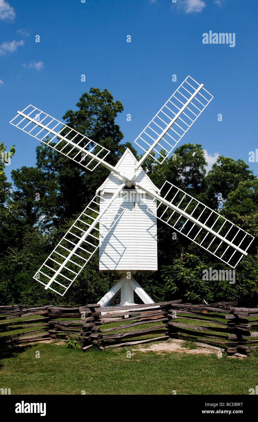A white wooden windmill in a small meadow behind a wooden fence on a summer day with blue skies surrounded by trees - Stock Image