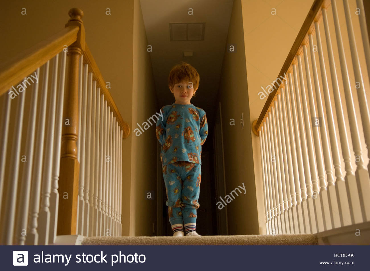 A 3-year-old boy plays on the stairs of his home. - Stock Image