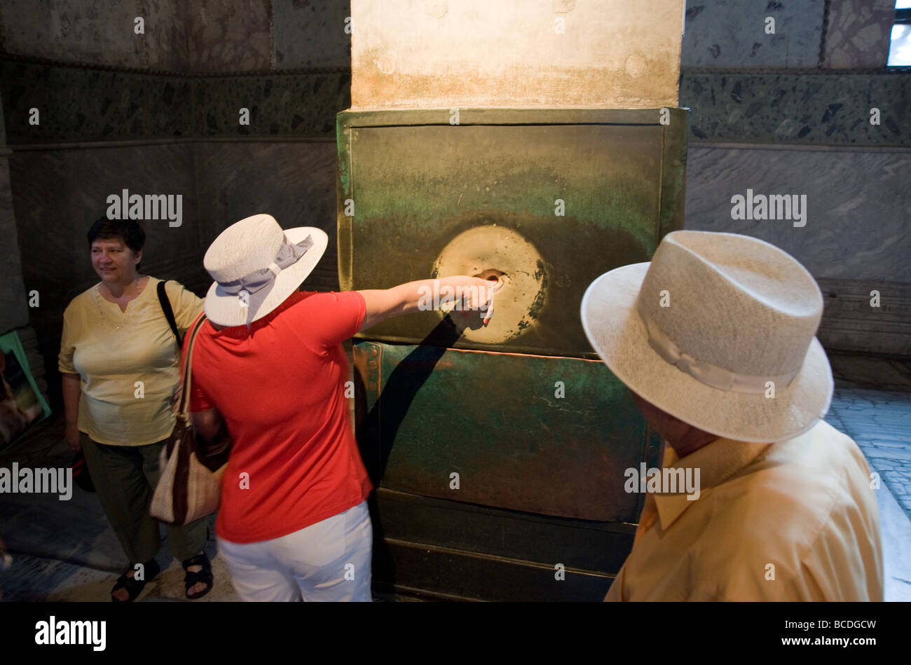 A tourist places her thumb in the wishing column and rotates her hand in Aya Sofya in Istanbul Turkey Stock Photo