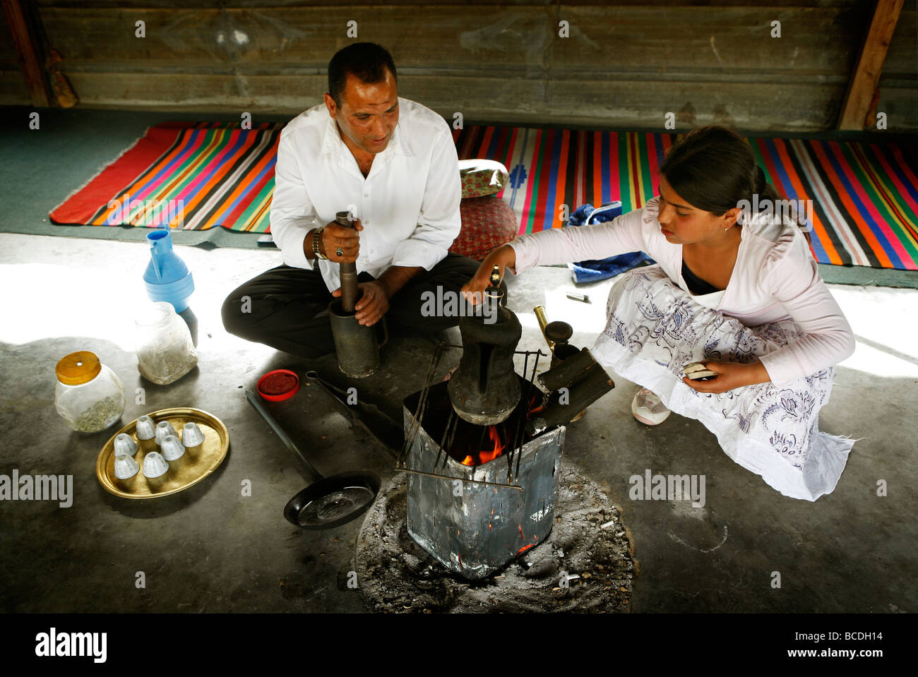 A Bedouin man and his daughter prepare traditional coffee in a tent in the unrecognized Bedouin village of El Araqeeb - Stock Image