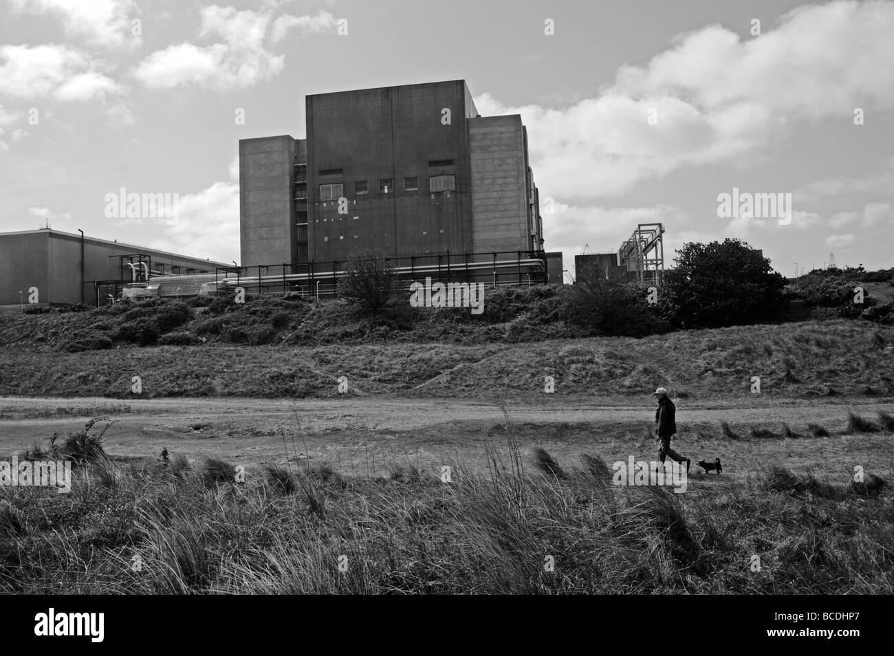 Black and white,man walking dog on beach in front of Sizewell A nuclear power station,Leiston,Suffolk,UK - Stock Image
