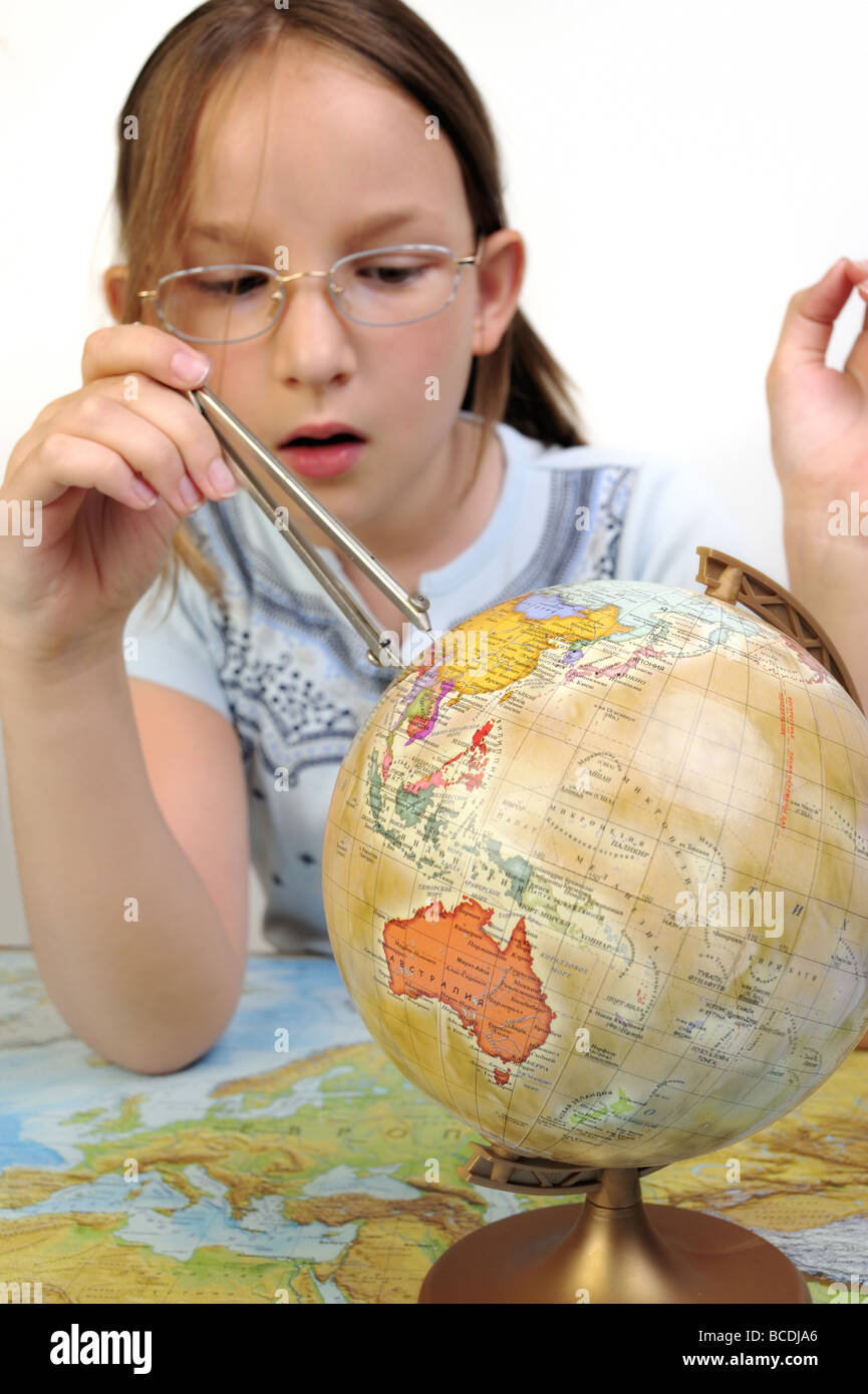 Teenage girl exploring the globe - Stock Image