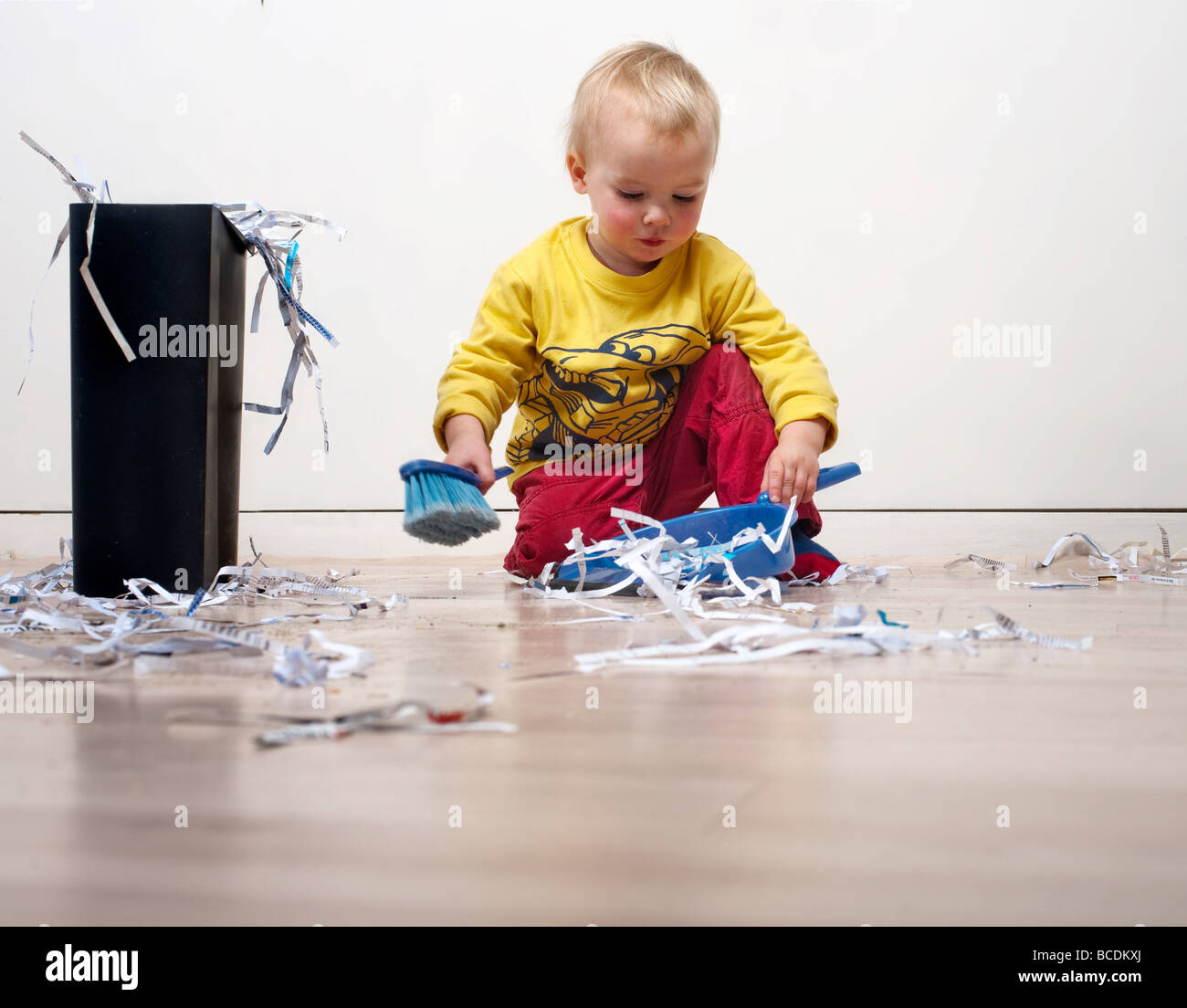 Young child cleaning up shredded papaer - Stock Image