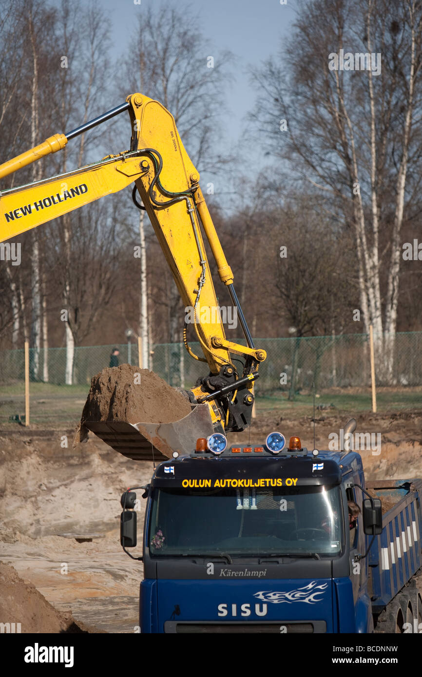 Digger loading dirt to dump truck , Finland - Stock Image
