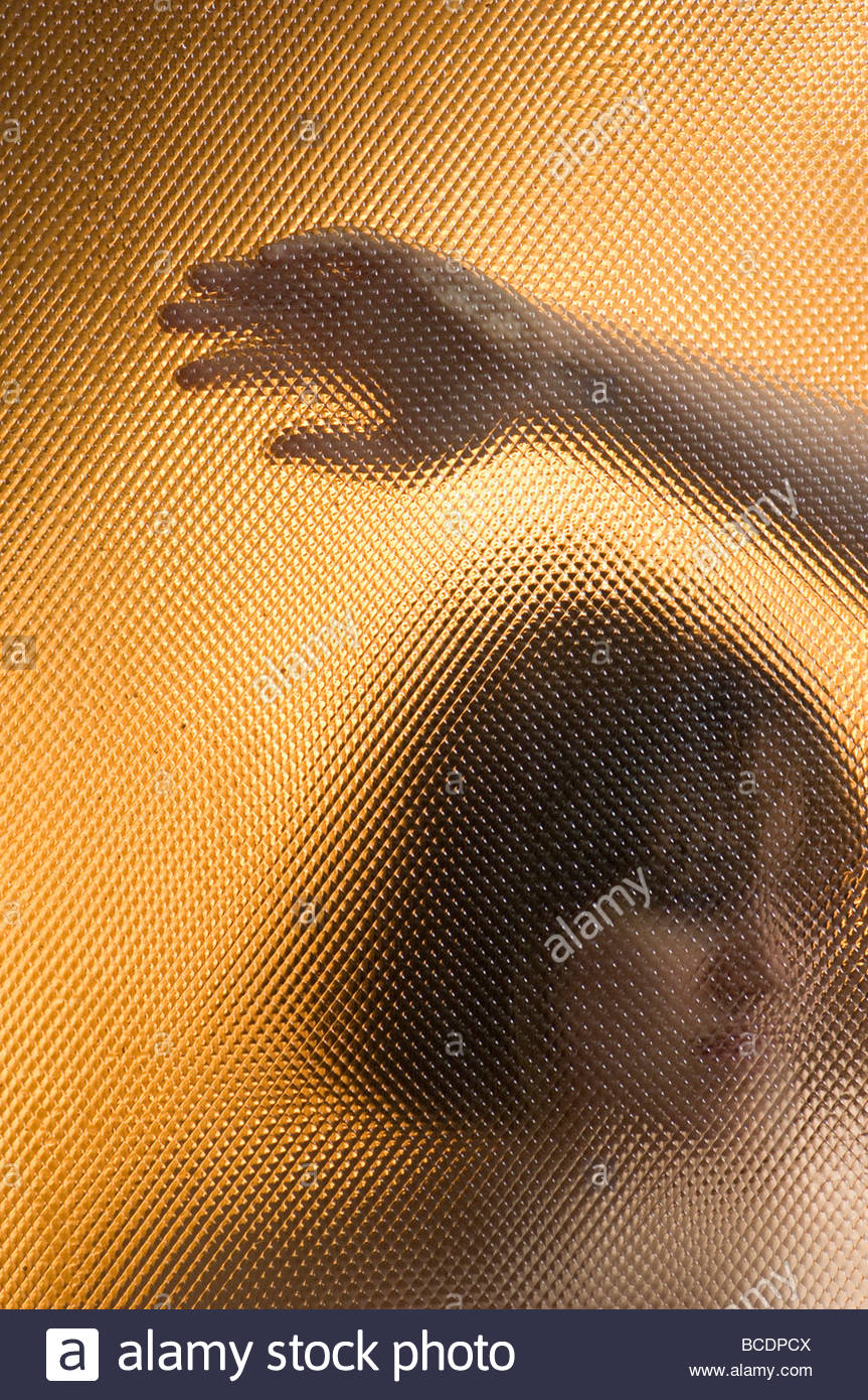 Portrait of a young woman looking through glass. - Stock Image