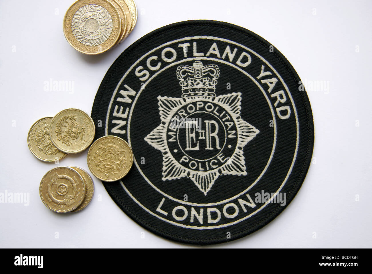 London Metropolitan Police New Scotland Yard patch and pound coins - Stock Image
