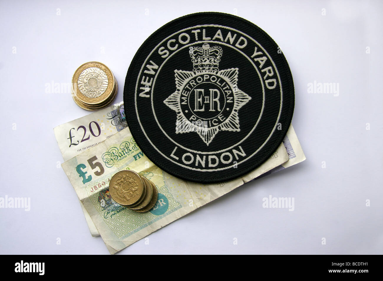 London Metropolitan Police New Scotland Yard patch and British money - Stock Image