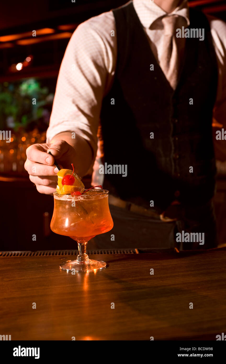 bartender making a drink at a bar. - Stock Image