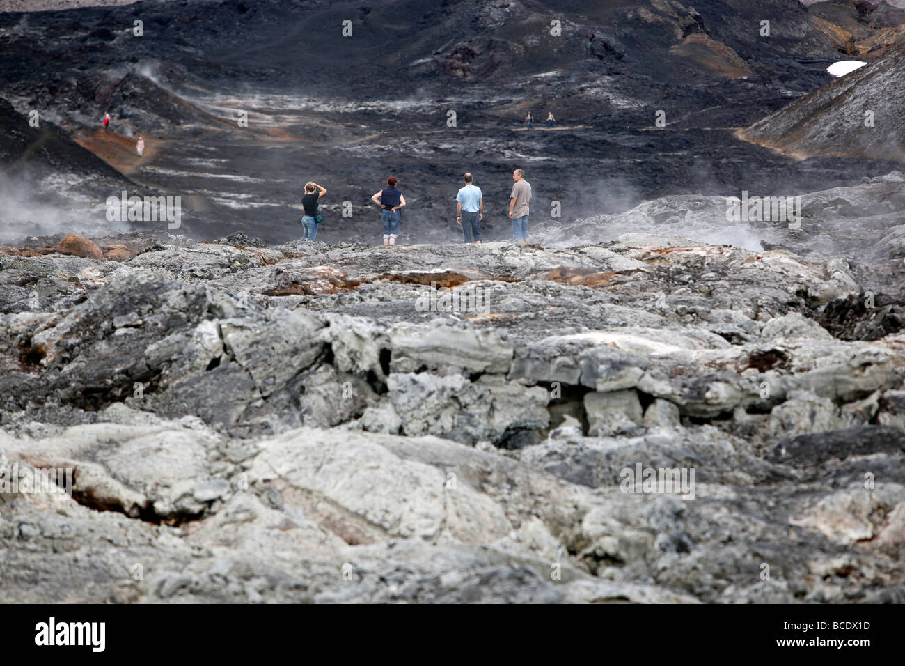 Four people look over a lava field, Krafla, Iceland Stock Photo