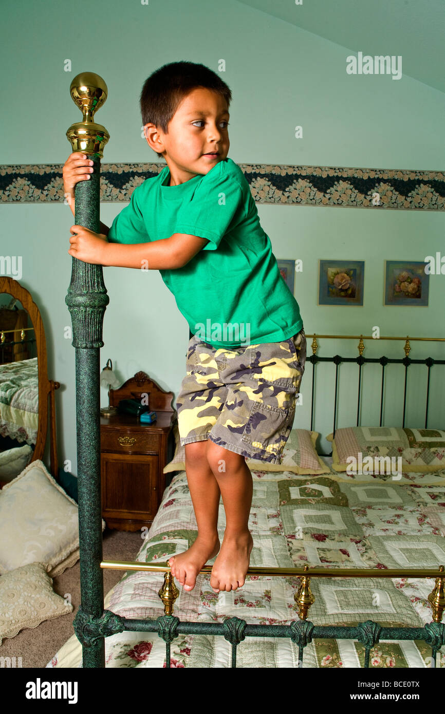 Young adventures adventure adventurous ethnic diverse  Hispanic boy 5-6-year old low angle from below climbing four - Stock Image