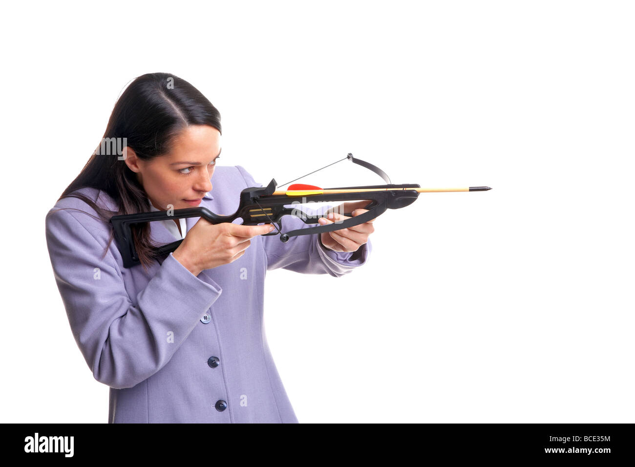 Businesswoman in a suit shooting an arrow from a crossbow as she aims at the target isolated on a white background - Stock Image
