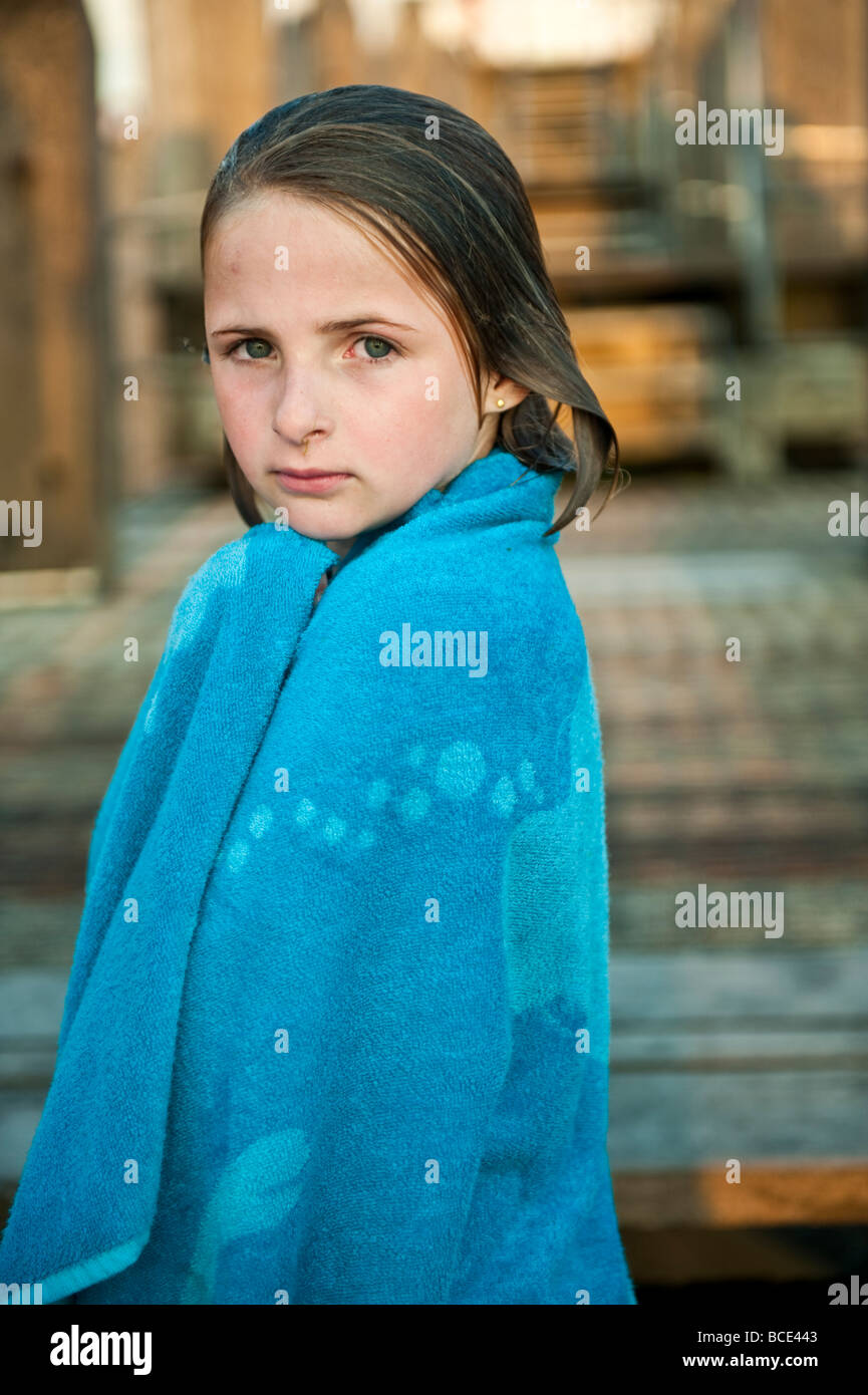 Ten year old girl wrapped in a blue towel after swimming in the sea wet hair looking at the camera - Stock Image