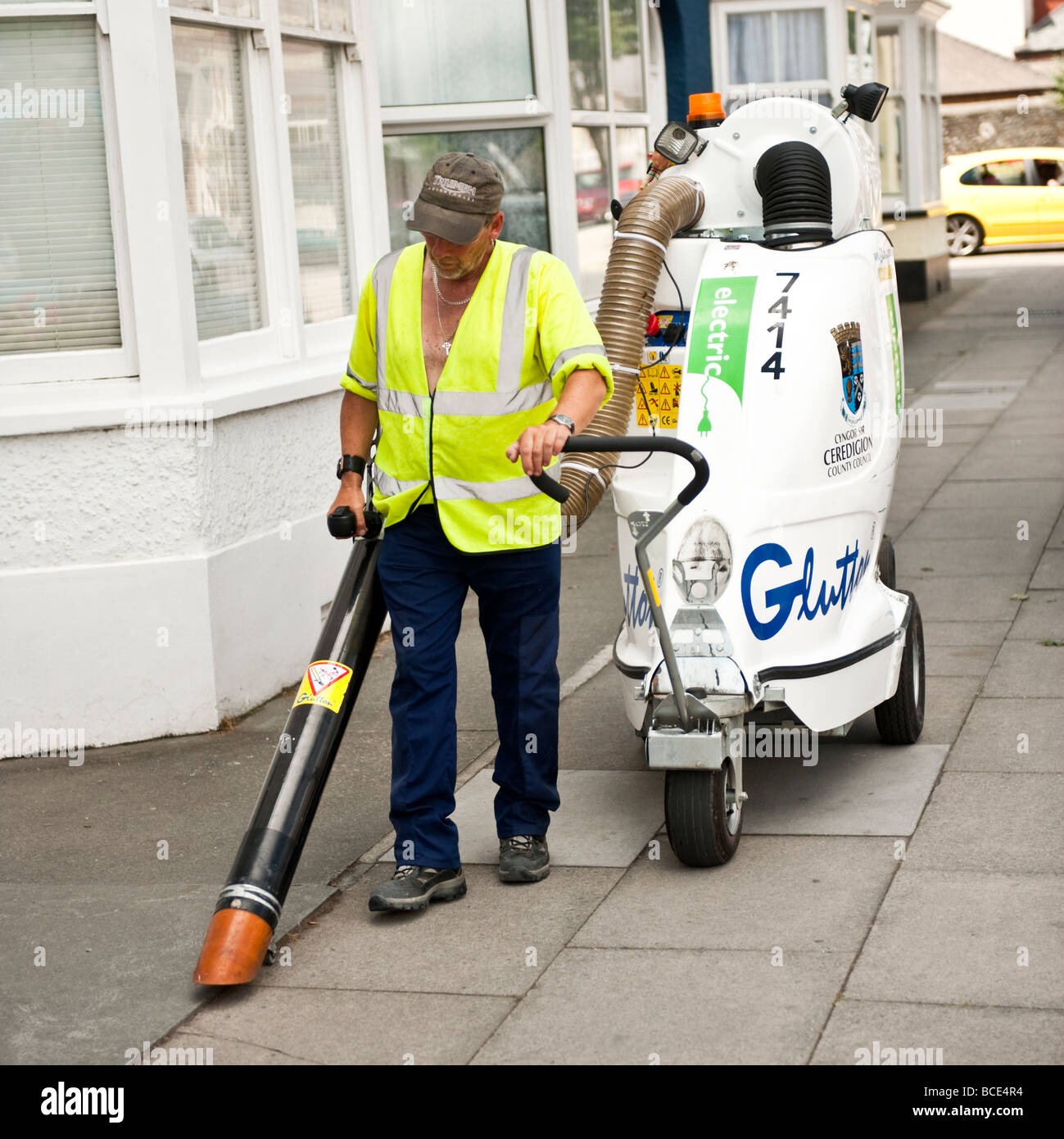 Local authority worker cleaning the streets using an electrical powered industrial scale Glutton vacuum cleaner - Stock Image