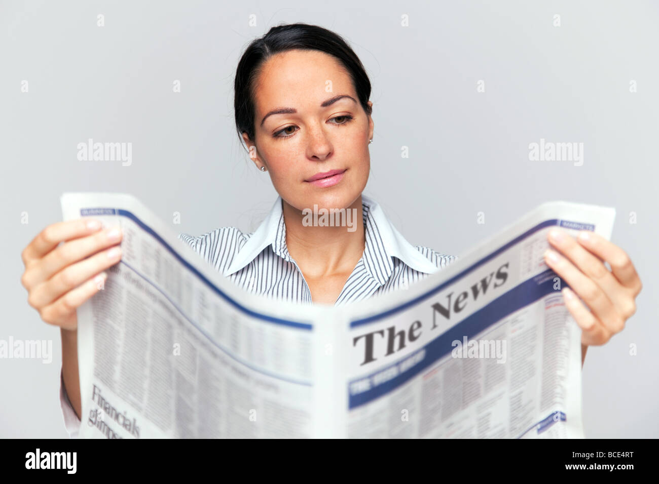 Businesswoman reading a newspaper focus is on her face and newspaper is blurred - Stock Image