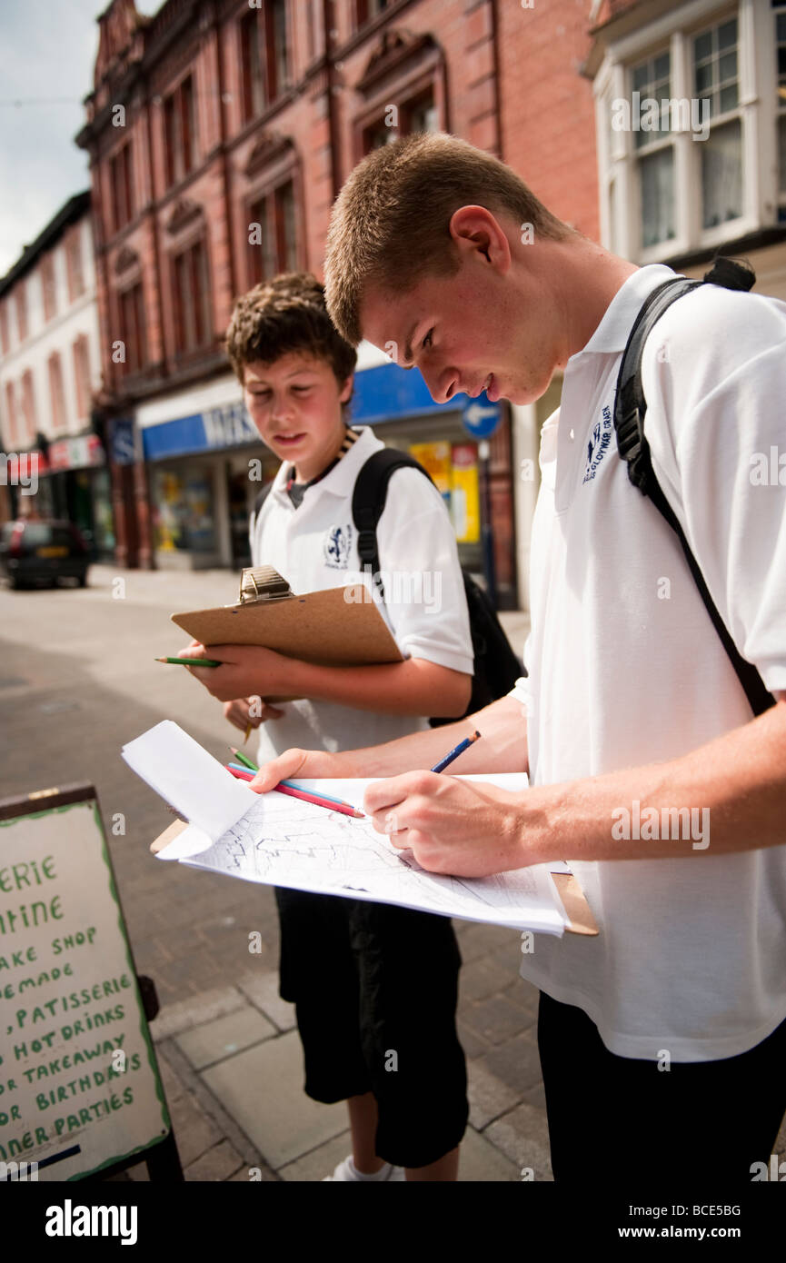 Two GCSE school children on an urban geography field course in a town land use mapping recording the types of shops - Stock Image