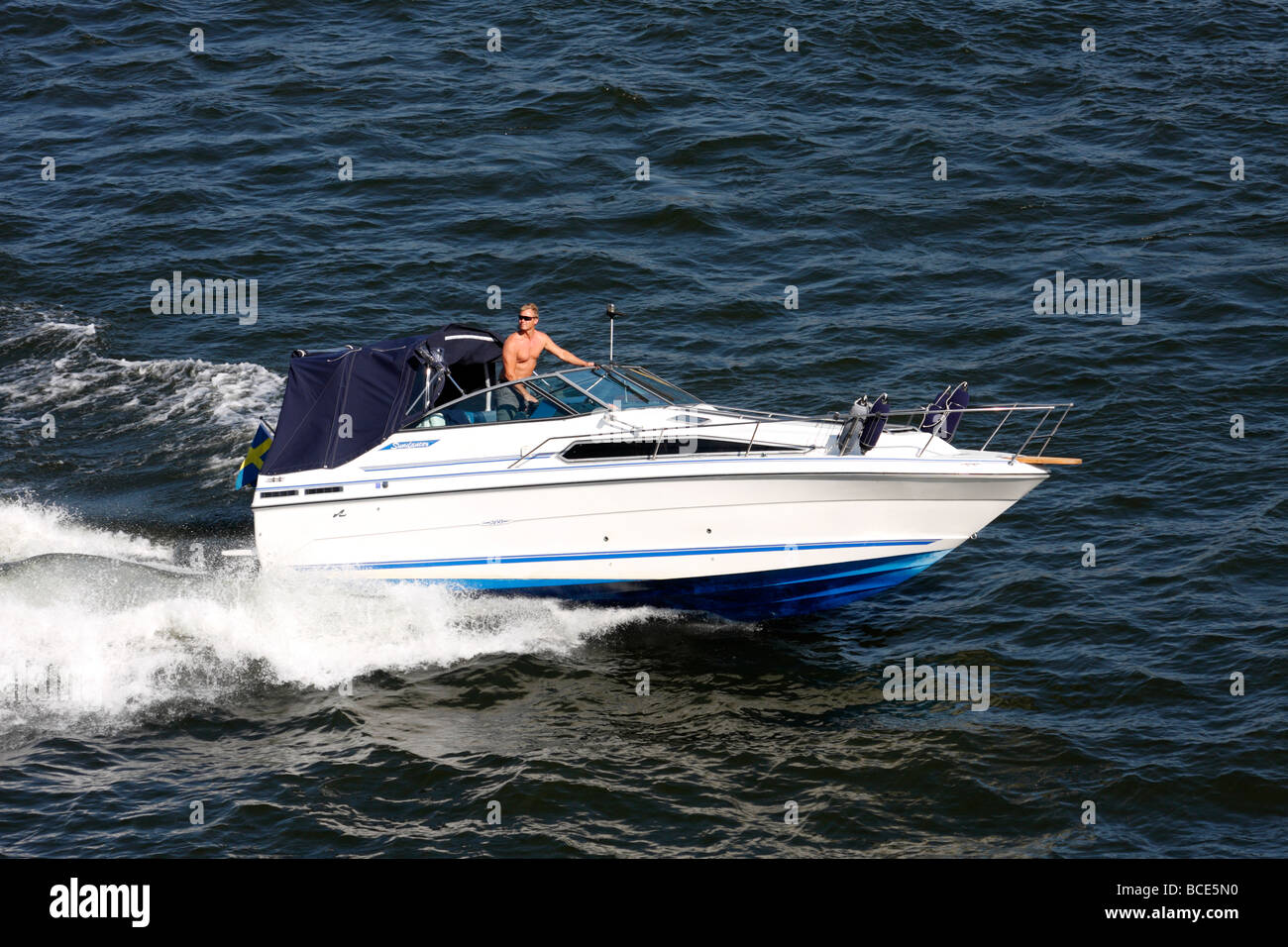 Man driving powerboat in Stockholm Harbor - Stock Image