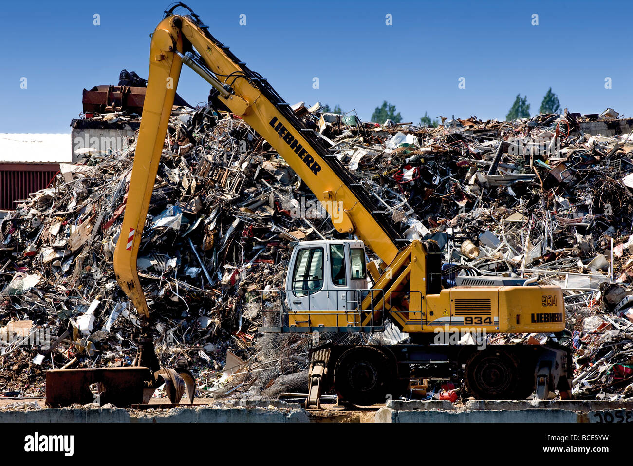 Mechanical digger in front of a waste stack in Copenhagen harbour - Stock Image