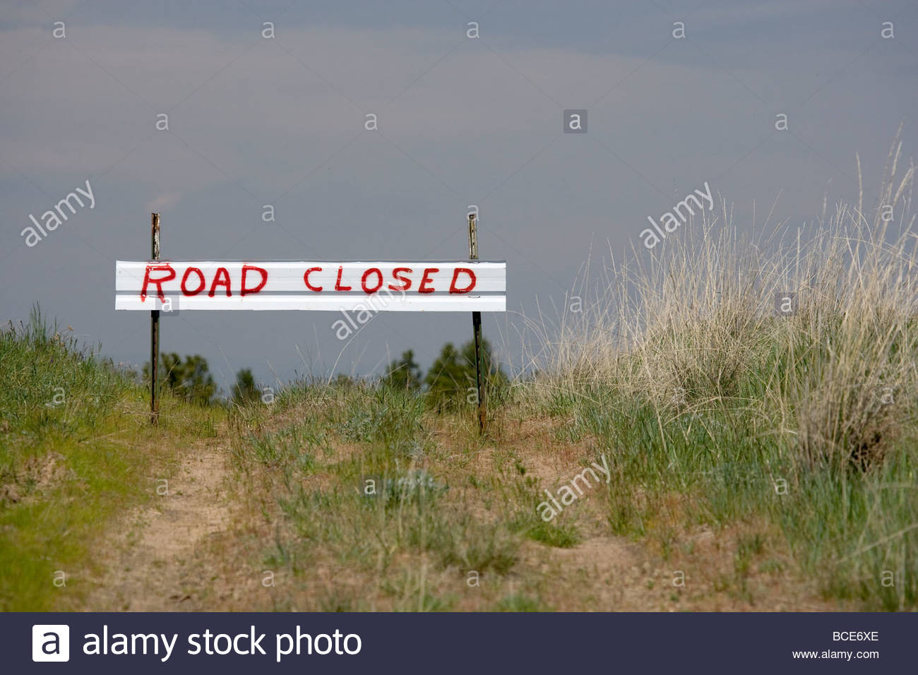 A 'Road Closed' sign keeps cars from visiting a ghost town. - Stock Image