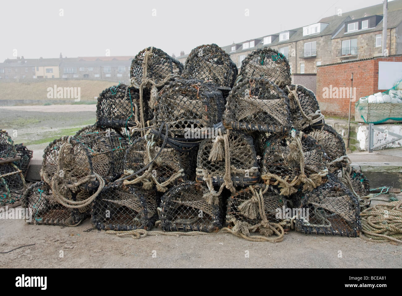 Crab Pots Stacked on Quay at Seahouses - Stock Image
