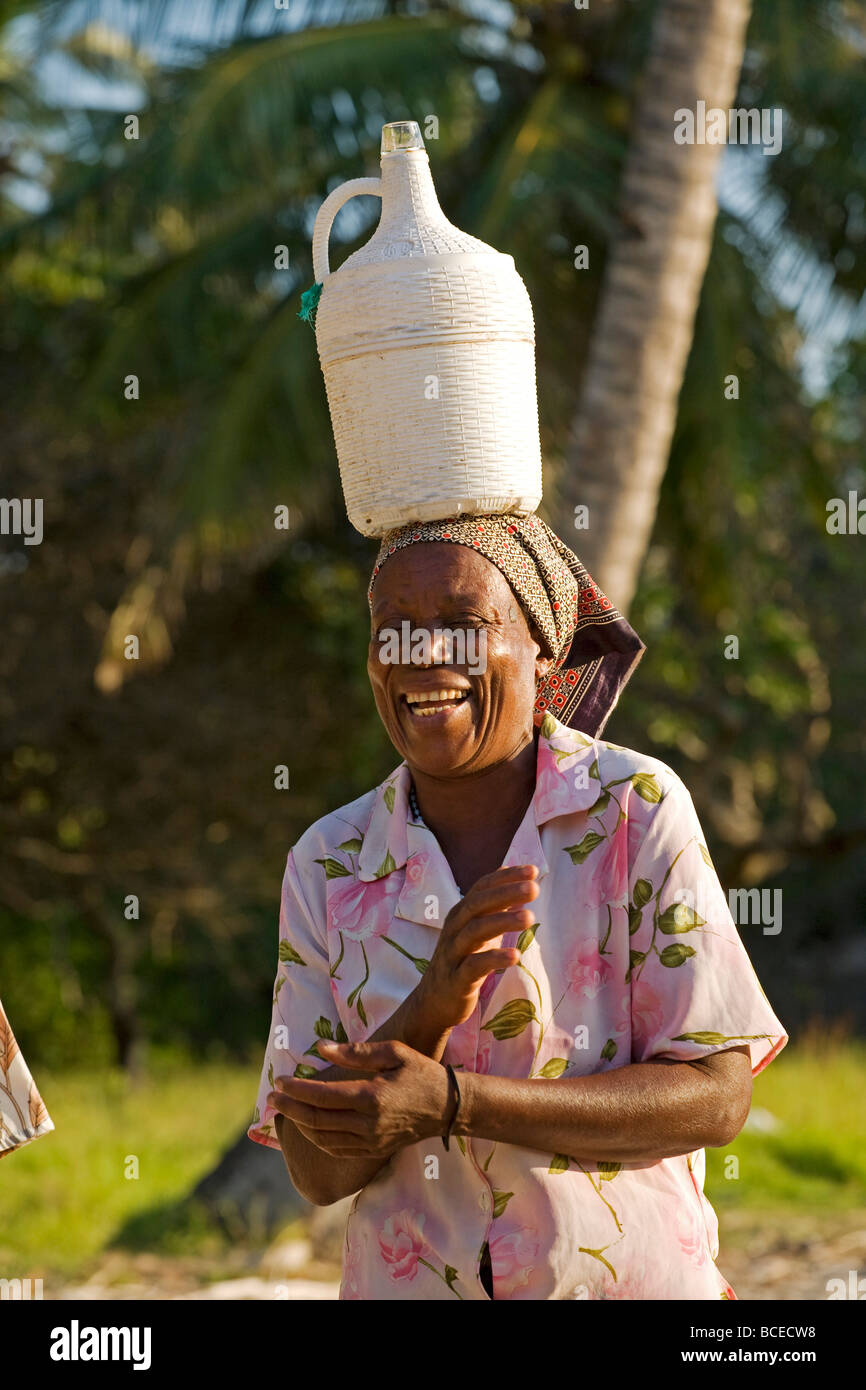 Mozambique, Inhaca Island. An african lady on the Island of Inhaca in Mozambique carrying home made wine. Stock Photo