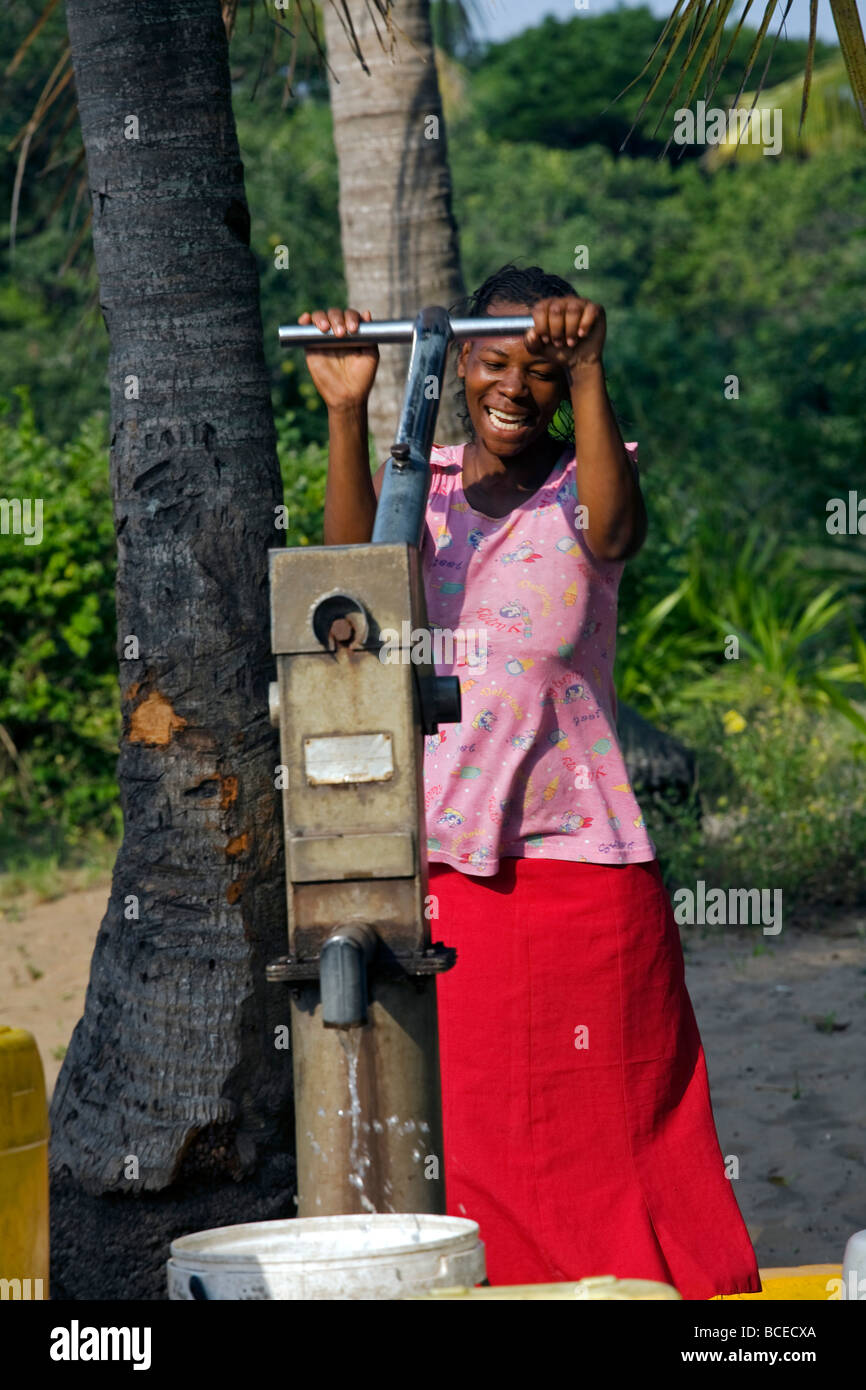 Mozambique, Inhaca Island. An African woman pumps water at a well on the island of Inhaca. Stock Photo