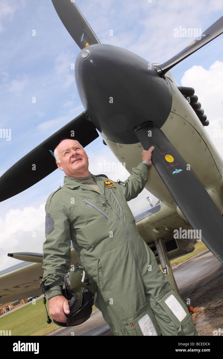 Lt Cdr John Beattie famous pilot and aviator stands in front of a warbird Supermarine Seafire that he pilots - Stock Image