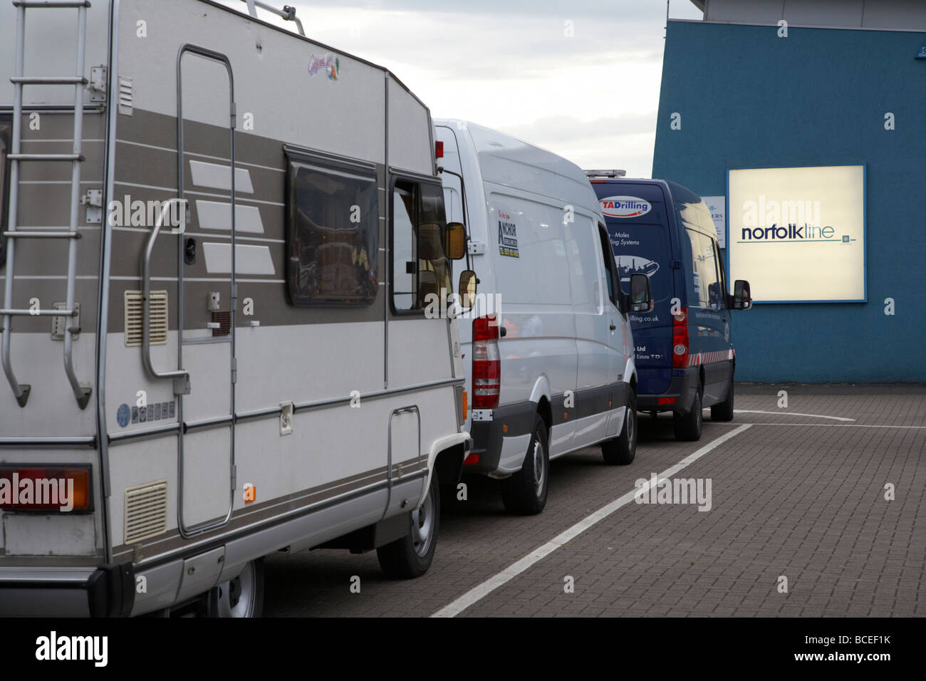 camper van and vans queuing in line to board the norfolkline belfast to liverpool ferry at the terminal in belfast - Stock Image