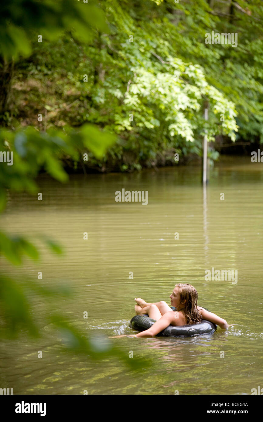 Teenage girl floats on an innertube near a wooded area - Stock Image