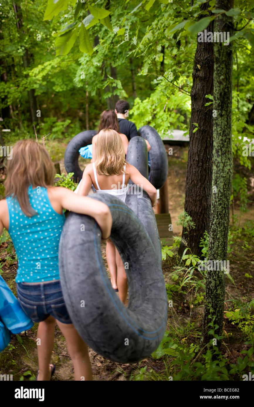 Teenagers carrying innertubes - Stock Image