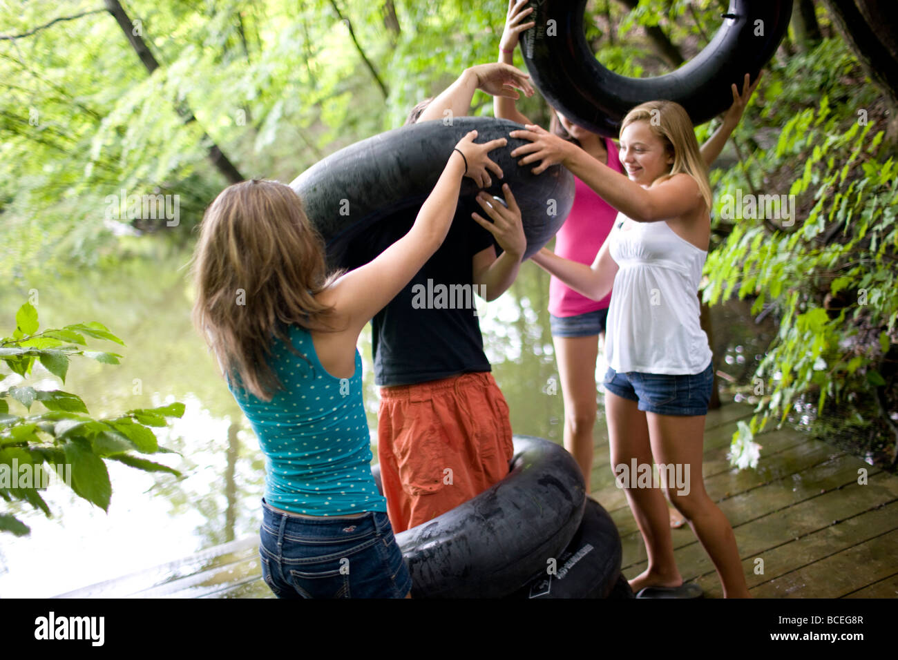 Group of teenagers playing around with innertubes - Stock Image