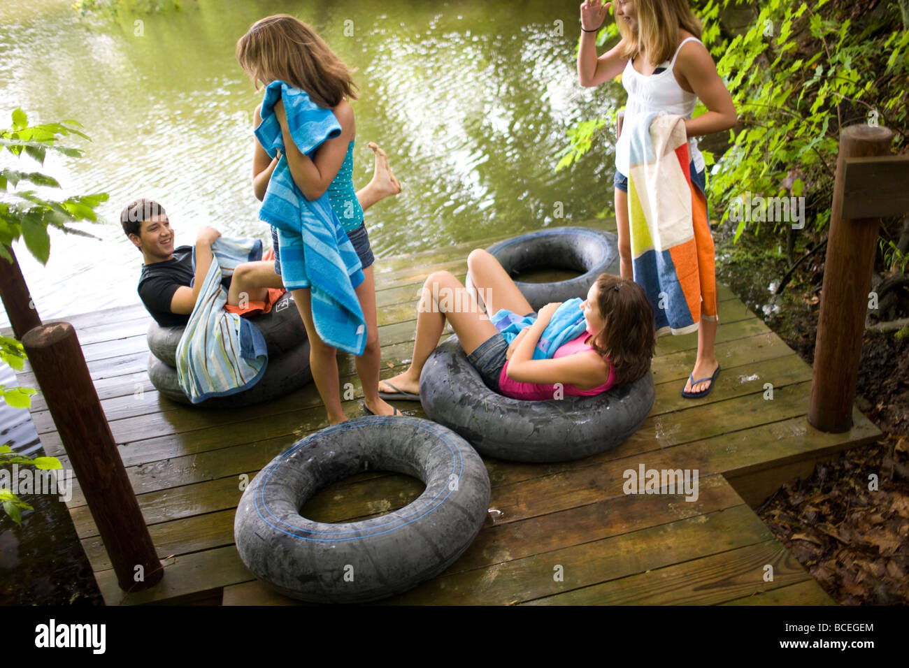 Group of teenagers hanging out near a lake with innertubes - Stock Image