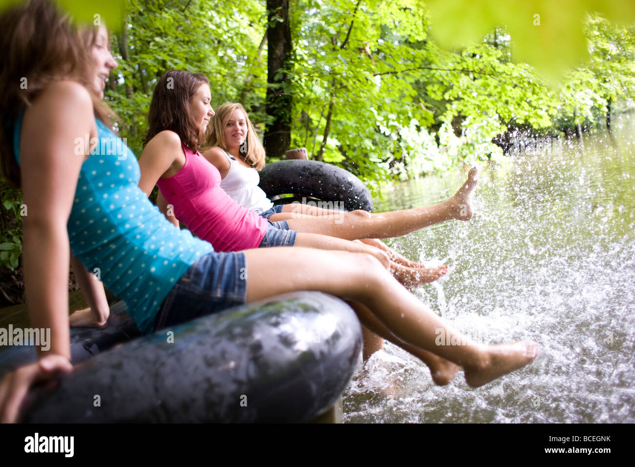 Teenage girls sitting in innertubes and splashing water - Stock Image
