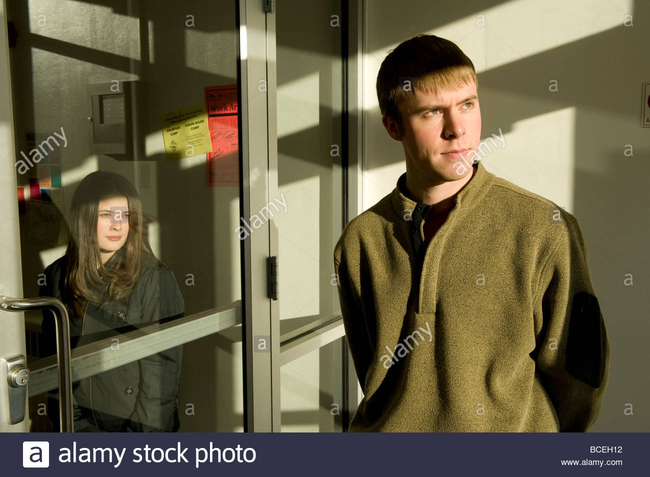 Two young college students gaze off into space. - Stock Image