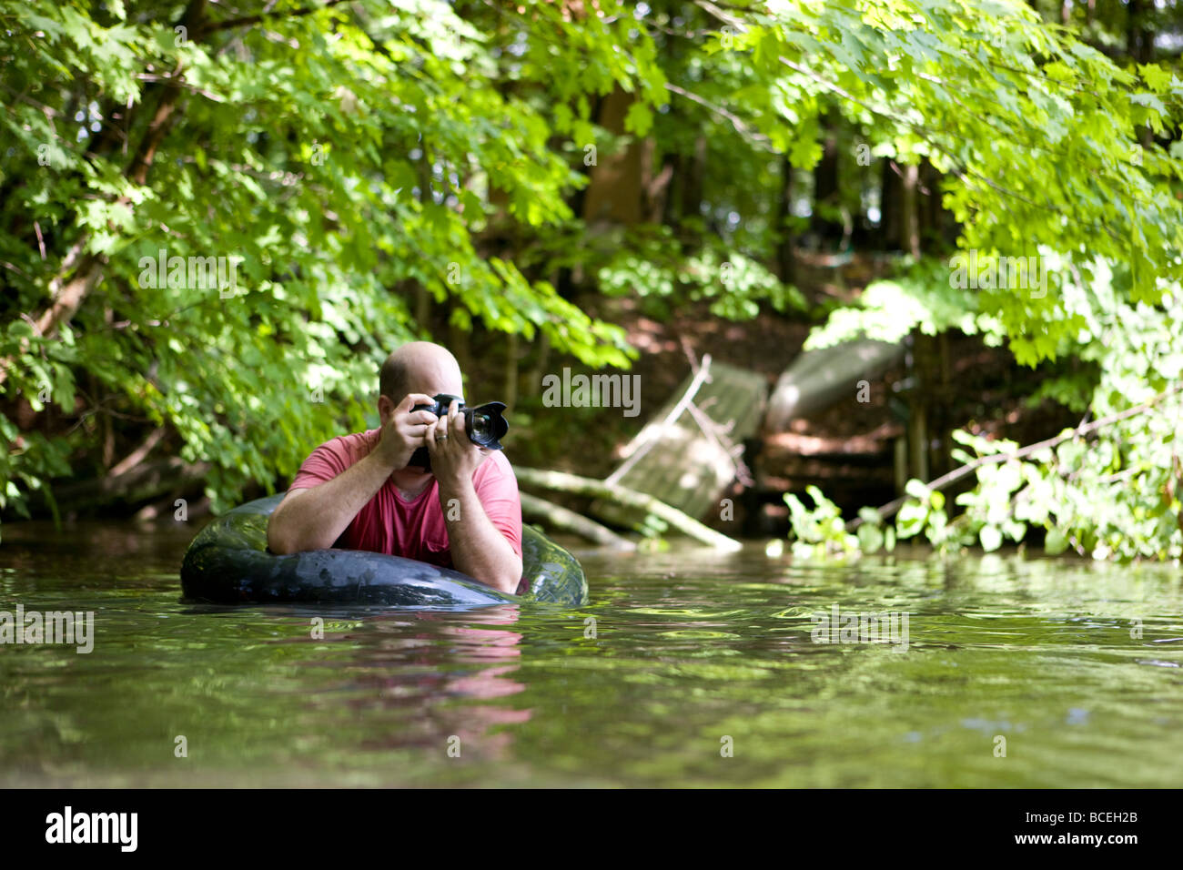 Man photographing from the water in an innertube - Stock Image