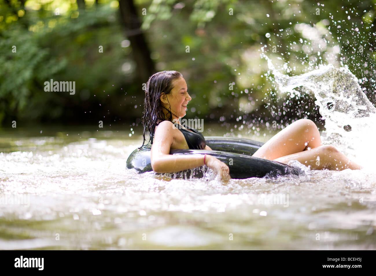 Teenagers splashing water while sitting in innertubes - Stock Image