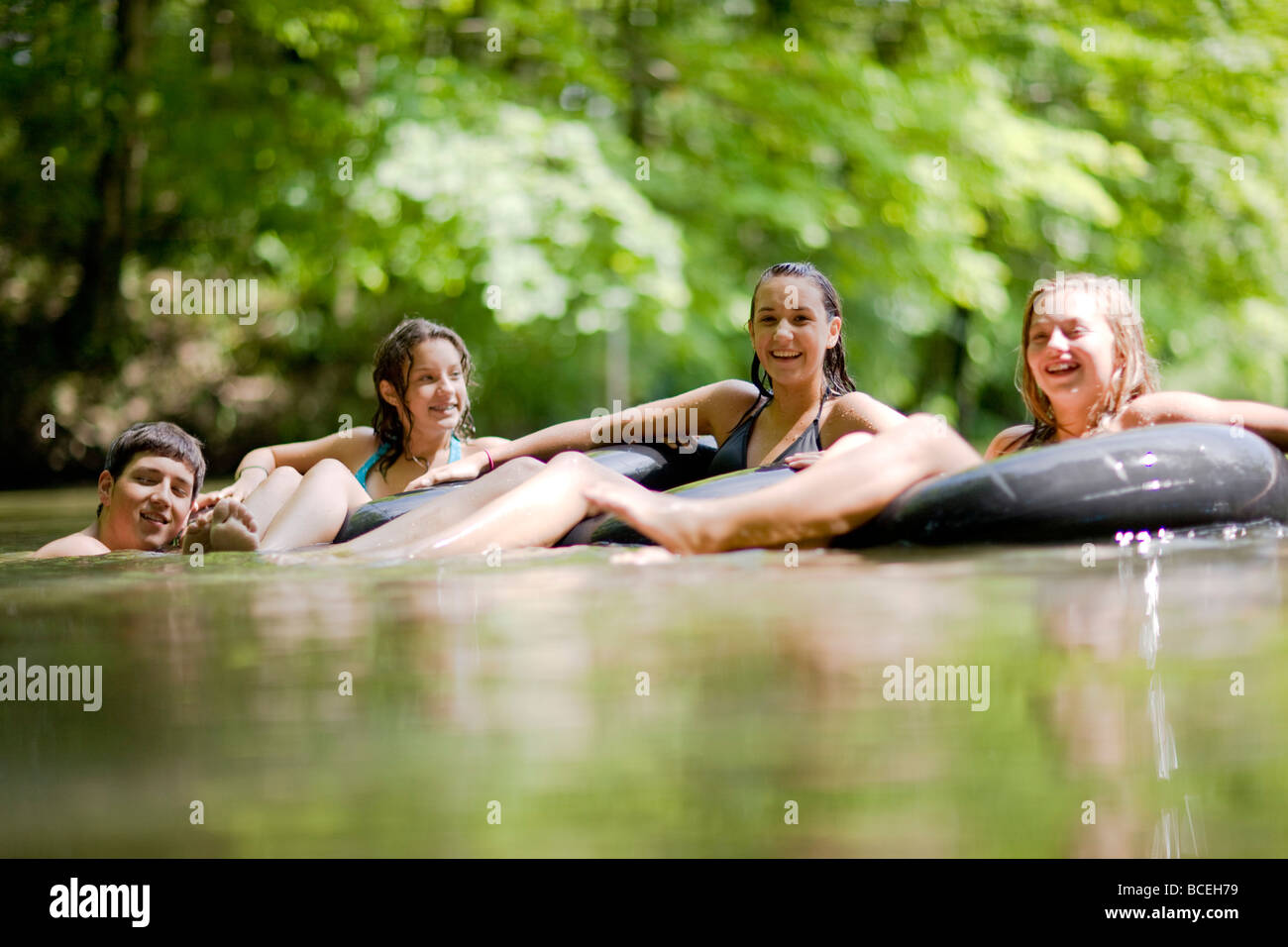 Teenagers sitting in innertubes in the water Stock Photo