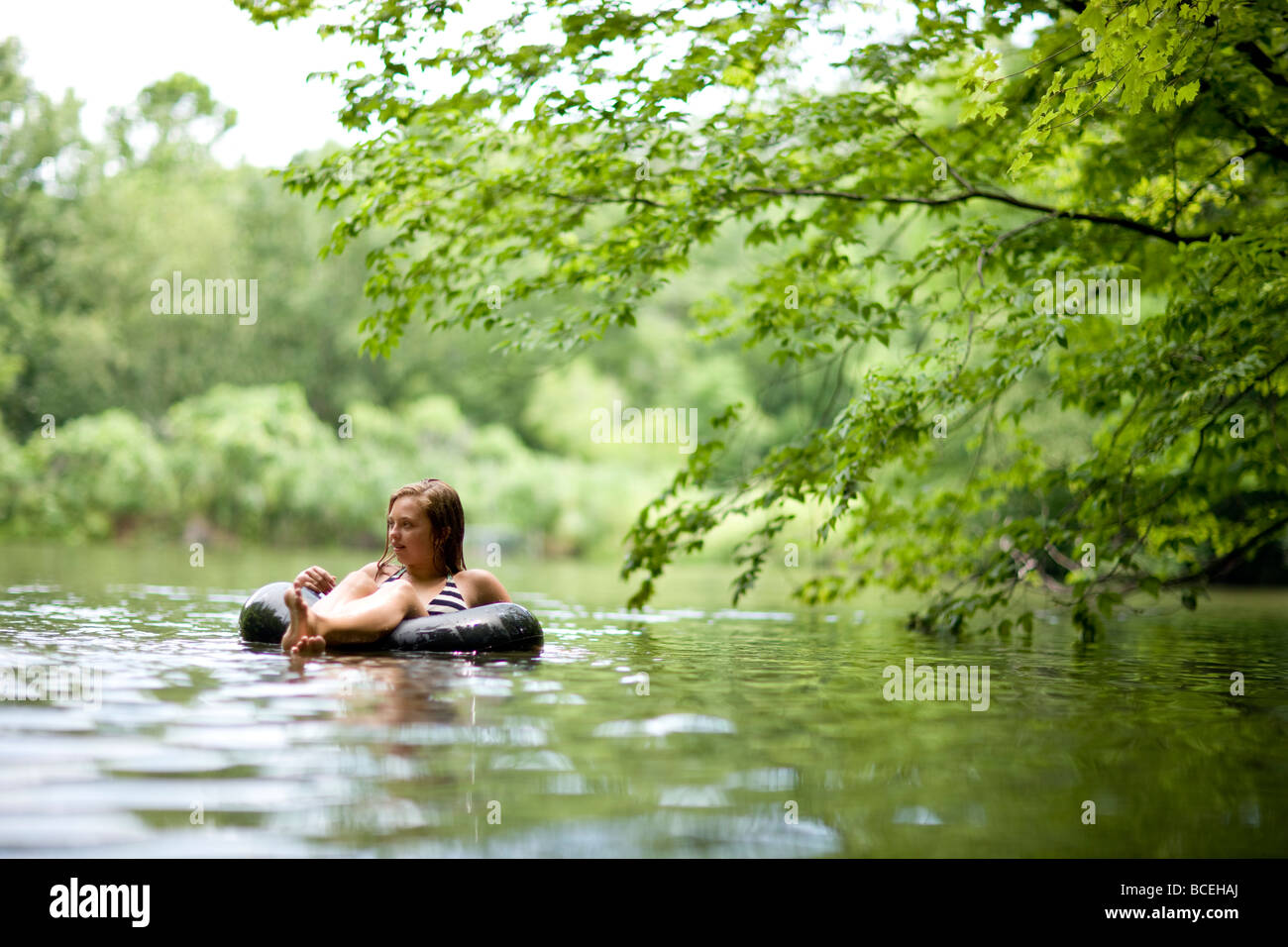 Teenage Girl sitting alone in the water in an innertube - Stock Image