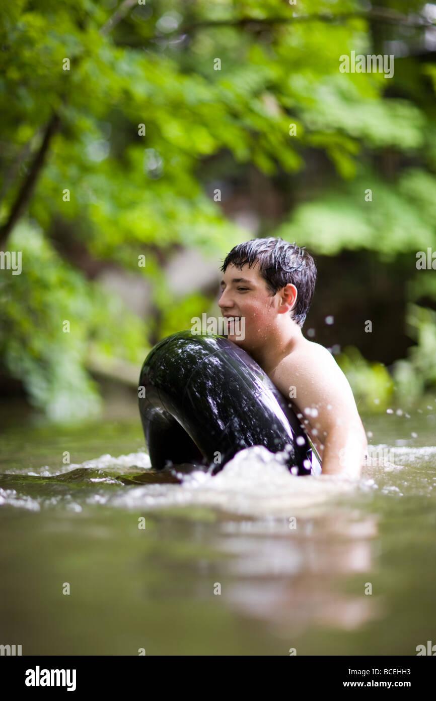 Teenage boy floating in an innertube in the water Stock Photo