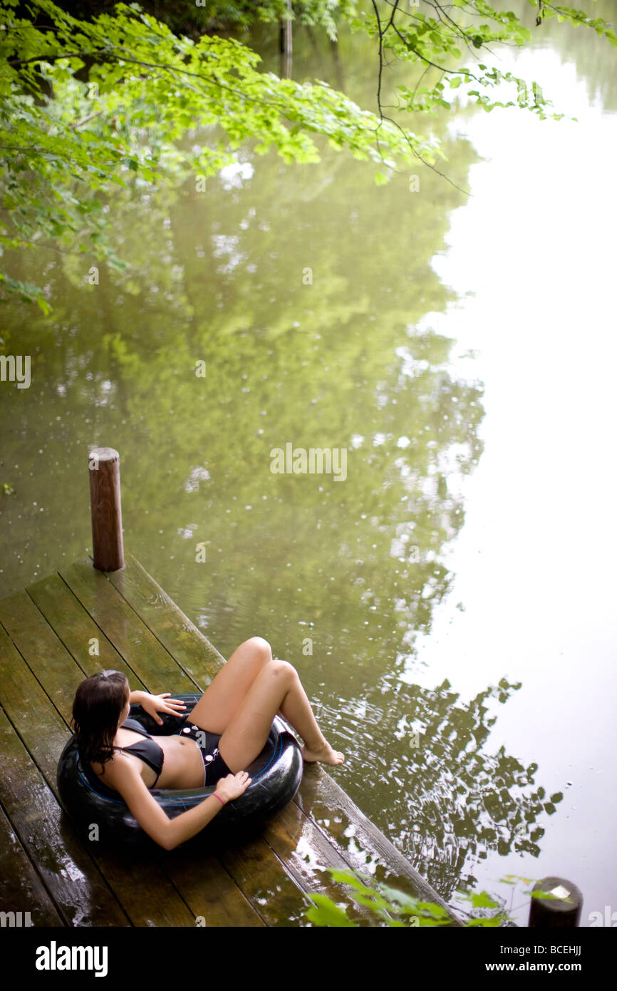 Teenage girl sitting in an innertube on the edge of a dock - Stock Image