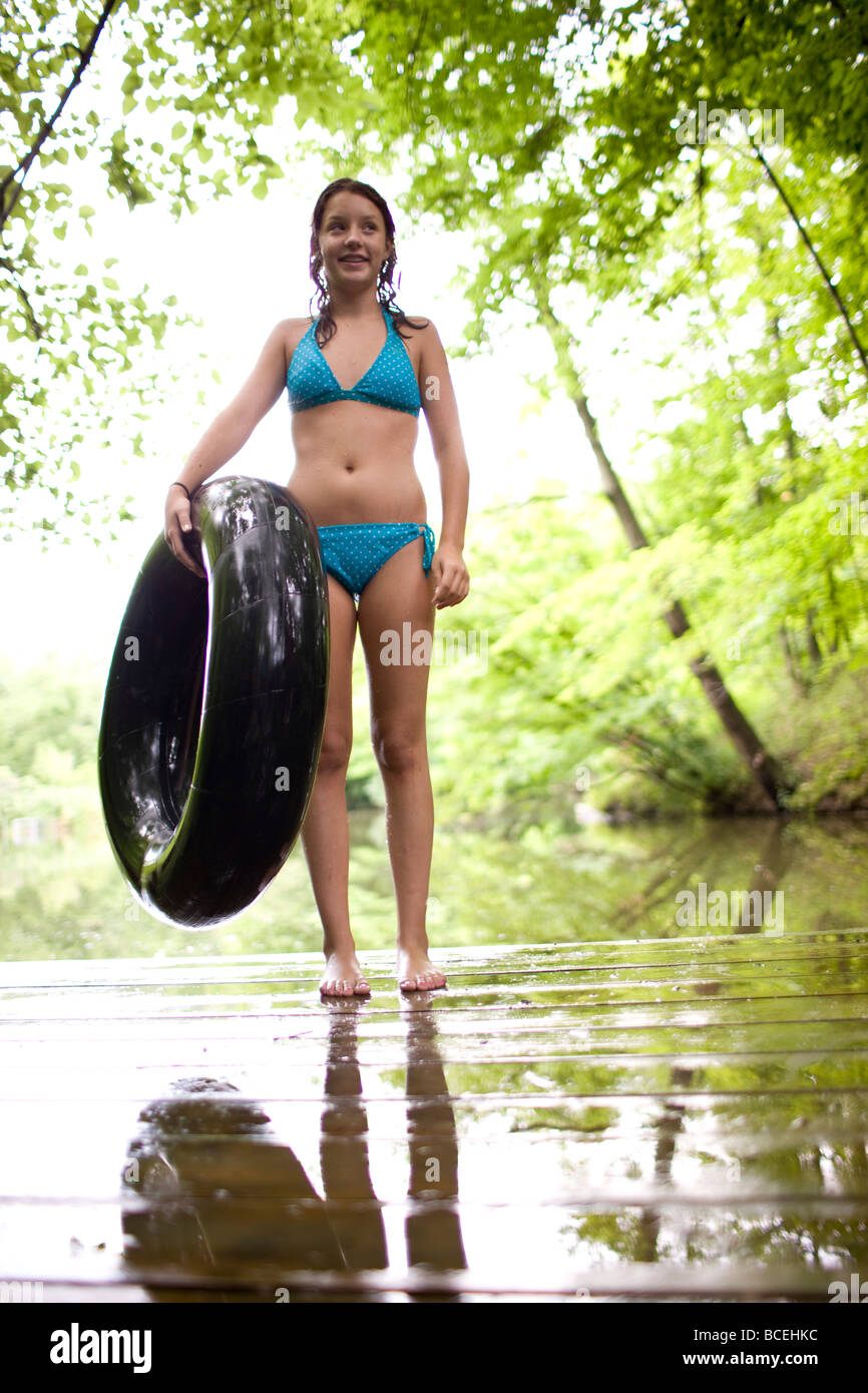 1dfc53d38e6 Teenage girl wearing a bathing suit holds an innertube - Stock Image
