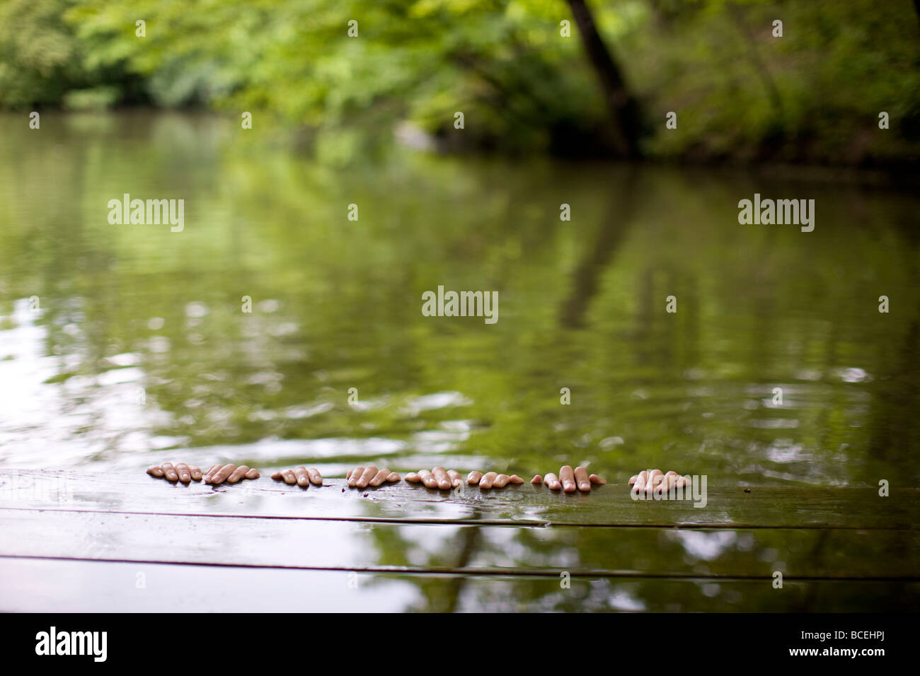 Hands hanging off the side of a dock - Stock Image