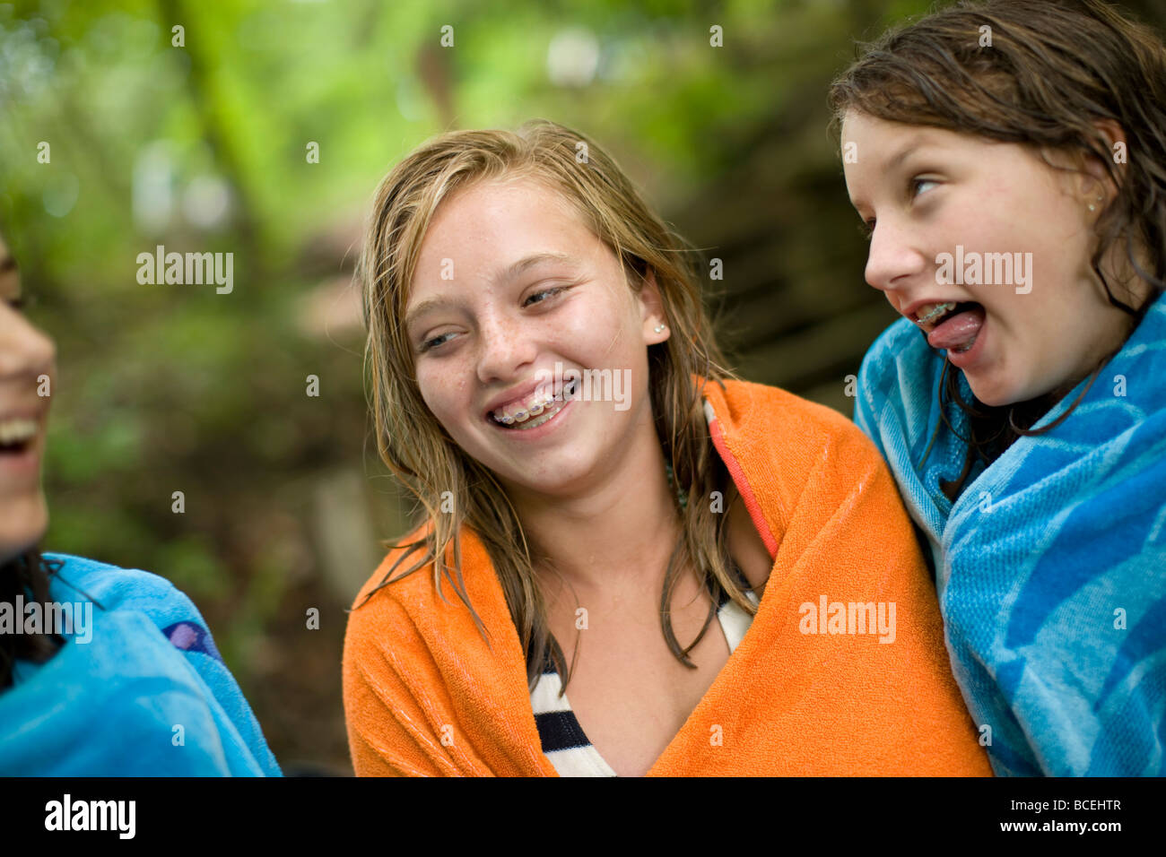Teenage girls are laughing and having fun while wrapped up in beach towels - Stock Image