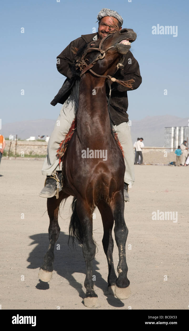 A proud Afghan horseman restrains his lively stallion as he shows it off on the Teppe Maranjan plateau in Kabul - Stock Image