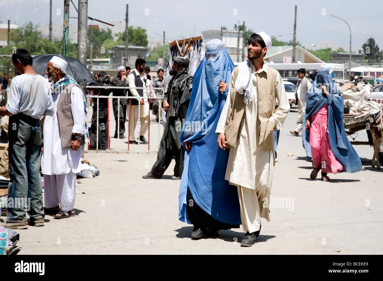 A young couple, the woman in the standard blue burqa, walking a busy street in Kabul, Afghanistan's capital - Stock Image
