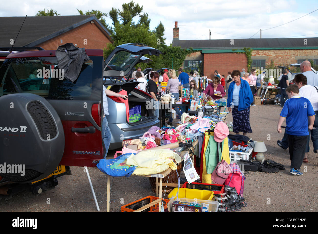 stalls and people browsing at a car boot sale in newtownabbey northern ireland uk - Stock Image
