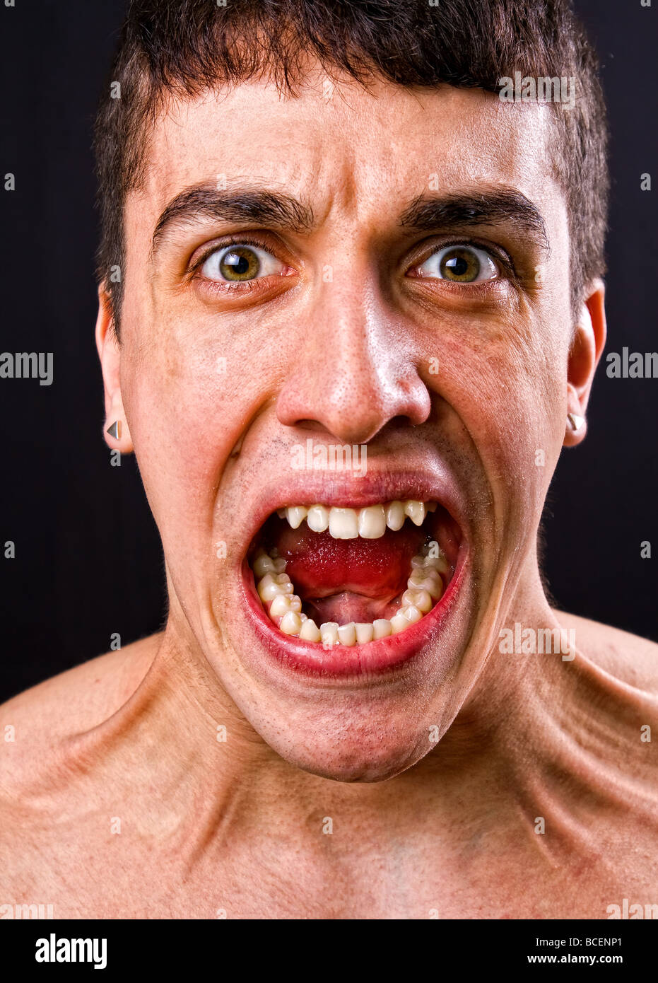 Scream of shocked and scared young man - Stock Image