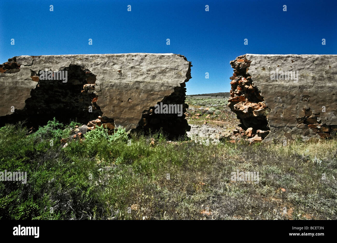 Desert floodwaters demolish a hole in a nineteenth century dam wall. - Stock Image