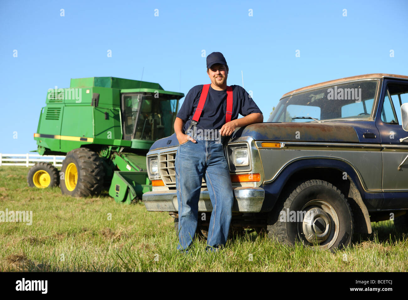 Portrait of farmer standing by truck - Stock Image
