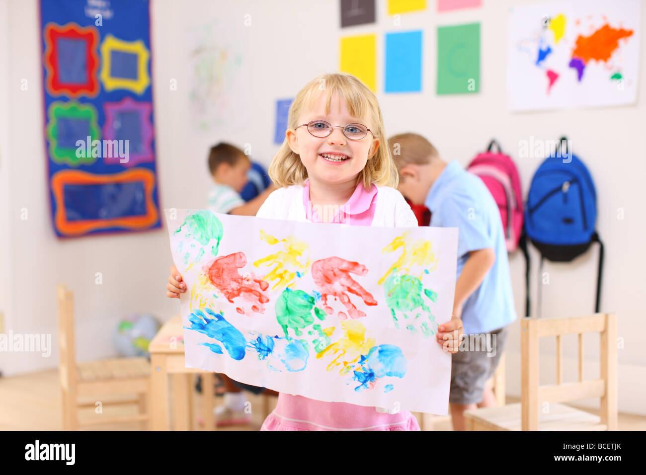 Preschool girl holding up artwork - Stock Image